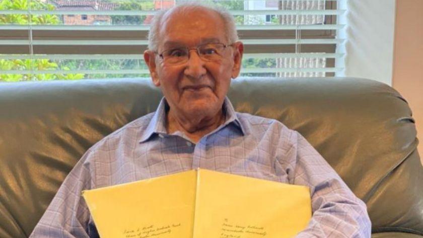 Lucio Caicedo de 104 años posando con su tesis.